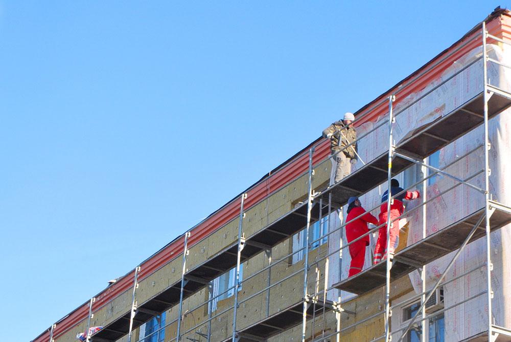 Des ouvriers sur un échafaudage en train de rénover la façade d'un batiment